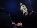 An indifinited person with Anonymous mask and notebook